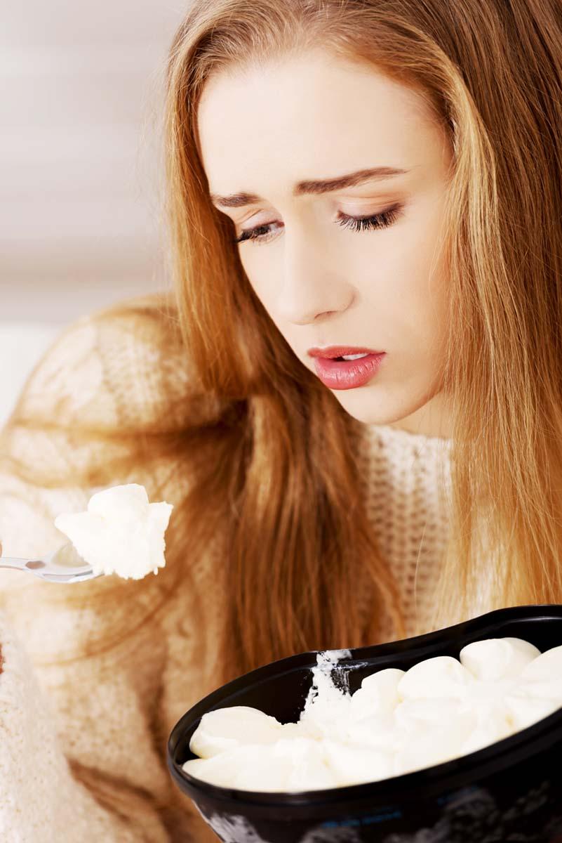 Frau mit deprimiertem Gesichtsausdruck und Essen in der Hand